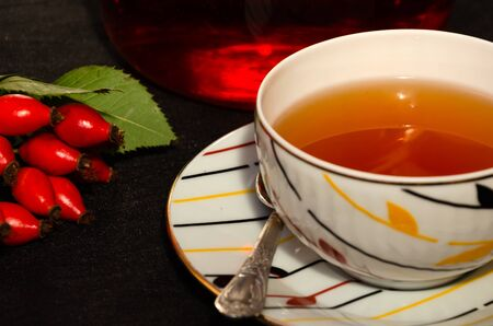 Tea with rose hips on a black background. White porcelain cup and a sprig of fresh ripe rosehip berries. Copy space. Closeup Banque d'images