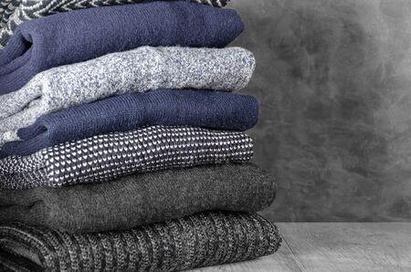Pila de suéteres de hombres de punto cálido doblado sobre fondo gris. Copie el espacio. De cerca