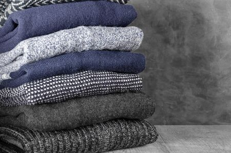 Stack of folded warm knitted men's sweaters on gray background. Copy space. Closeup