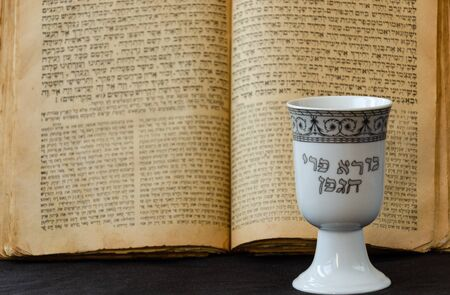 An open old Jewish Bible and white porcelain kiddush wine cup on black background. An open scripture page. The inscription on the cup in Hebrew: Creator of the fruit of the vine. Selective focus