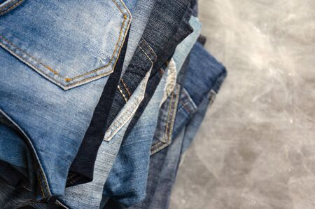 A stack of carelessly folded jeans on gray background. Close-up of jeans in different colors. Jeans texture or denim background. Copy space. Selective focus