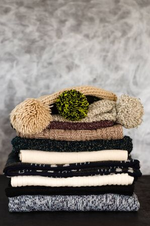 A stack of neatly folded knitted winter scarves and hats on gray background. Season of warm clothes. Winter is coming. Close-up. Copy space