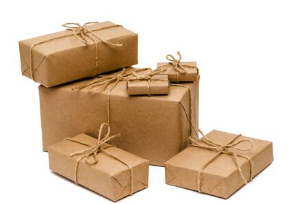 Pile of stacked boxes wrapped with brown kraft paper and tied with twine on a white background. Delivery, moving, package and gifts concept. Closeup