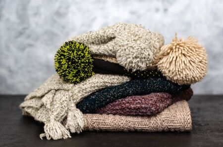 A stack of folded knitted winter scarves and hats on gray background. Season of warm clothes. Time to keep warm. Close-up
