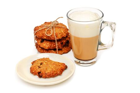 Transparent mug of coffee with milk, cappuccino or latte and homemade whole grain crispy oatmeal cookies with raisins. One cookie is bitten off. Concept of good start to the day. Close-up. Copy space