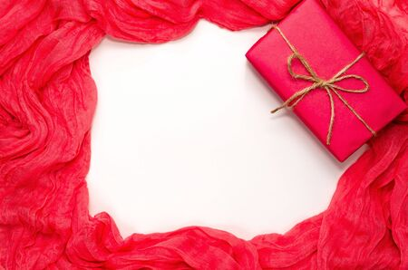 Festive composition. Pink gift box on soft folds of red coral fabric. Frame with space for text. Greeting card. Close-up. Flat lay, top view