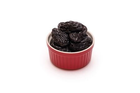 Prunes or dried plums in red ceramic bowl on white background. Natural healthy sweets concept. Close-up. Copy space