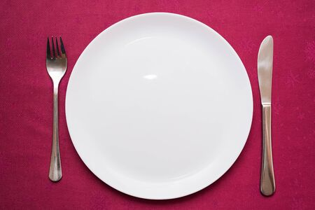 Empty white plate, fork and knife on maroon tablecloth. Elegant table setting. Top view, close-up
