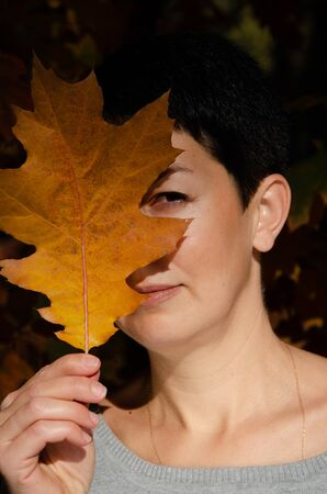 Young beautiful short-haired brunette woman is hiding her eye behind an autumn leaf in park. Closeup