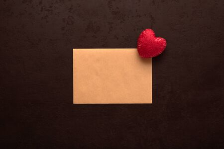 Red heart on blank kraft card for Valentines day message on black background. Declaration of love concept. Top view, flat lay 版權商用圖片