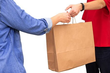 Female hand receiving package from delivery man. Young delivery courier dressed in red t-shirt holding brown paper bag isolated on white background. Delivery service concept. Copy space