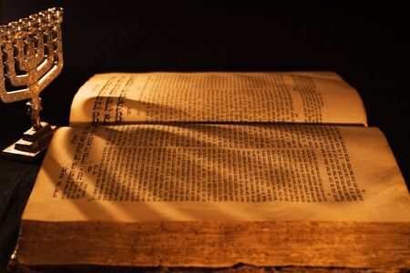 Hebrew Bible and silver menorah in light of burning candle on dark background. Shadow from menorah on open pages of Jewish prayer book in the darkness. Torah reading. Closeup Stock Photo