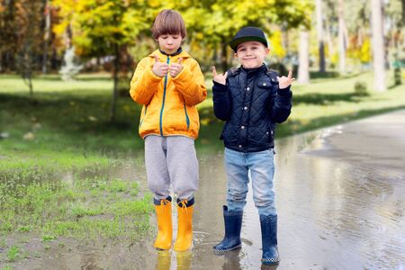 Two cheerfull friendly boys in rubber boots standing in puddle in park showing thumbs up gesture. Concept of social adaptation of autistic children. Friendship with peers. Full length portrait