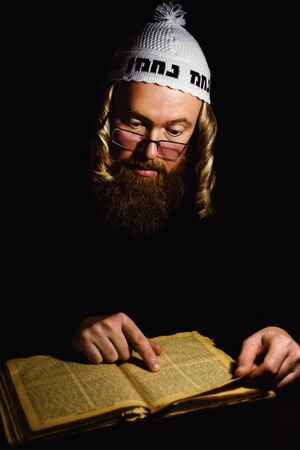 Hasidic jew reading Torah. Religious orthodox jew with sidelocks and red beard in white bale praying in the dark. Low key photo Stock Photo