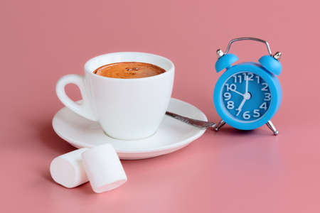 Morning cup of coffee, two marshmallows and blue alarm clock on pink background. 7 o'clock on clock face. Start of the day concept. Copy space
