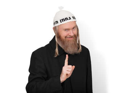 Smiling bearded jewish man with sidelocks in white kippah hinting do not try to deceive me. Charismatic sly jew dressed in black coat showing warning with finger on white background