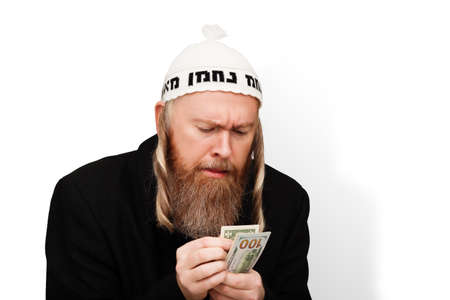 Greedy bearded jewish man counting his money. Thrifty jew with sidelocks in white yarmulke isolated on white background