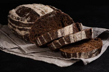 Artisan sliced rye bread. Closeup of slices of freshly baked sourdough bread on dark background. Low key. Selective focus