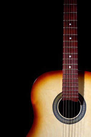 Acoustic guitar in white light. Isolated on black
