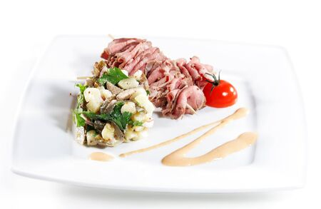 Roast Beef Served with Salad (Potatoes and Vegetables) and Cherry Tomato. Isolated on White Background photo