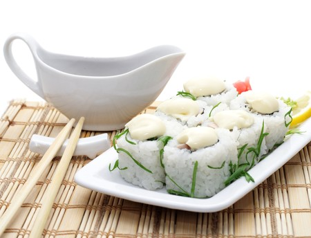 Rolls with Sauce and Greens on Bamboo Napkin Served with Soy Sauce an Chopsticks photo