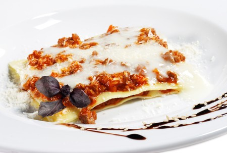 Meat Lasagna Served with Chocolate Decoration and Basil Leaves photo