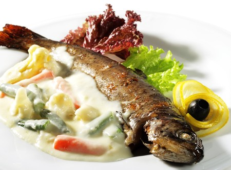 Fish Plate Served with Vegetables Sauce and Salad Leaves. Isolated on White Background photo