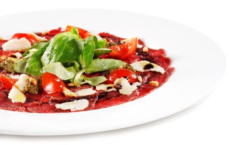 Beef Carpaccio with Greens and Tomato. Isolated on White Background photo
