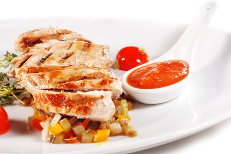 Fillet of Chicken with Vegetables and Cherry Tomato and Spicy Sauce. Isolated on White Background photo