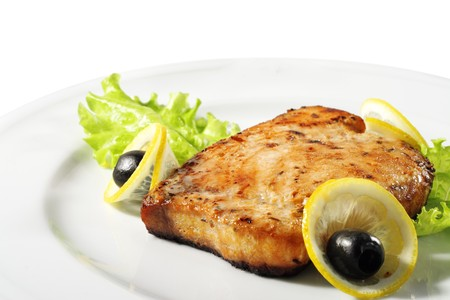 Fish Steak Served with Salad Leaves, Lemon and Olives. Isolated on White Background photo