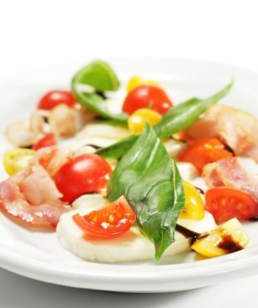 Salade de tomates cerise, Buffalo, fromage, bacon et les l�gumes feuilles. Isol� sur fond blanc Banque d'images