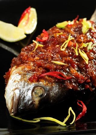 dorado: Thai Dorado wth Lemon Slice on a Black Dish