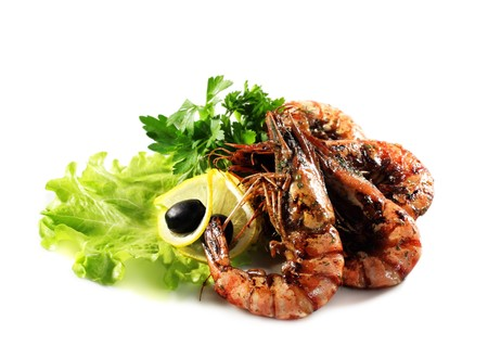 Seafood - Fried Shrimps Dressed with Salad Leaves, Parsley, Lemon and Olives. Isolated on White Background photo