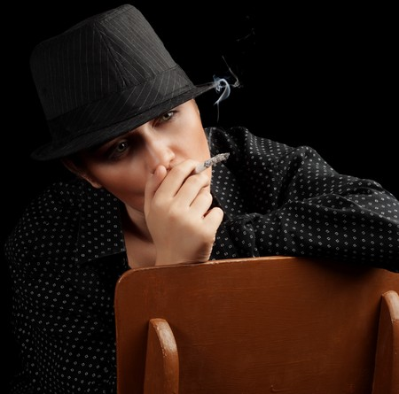 Smoked Woman in Black Hat. Isolated on Black Background photo