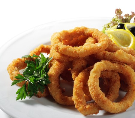 squids: Seafood - Fried Calamari. Deep-fried Squid Dressed with Salad Leaves, Parsley, Olives and Lemon. Isolated on White Background Stock Photo