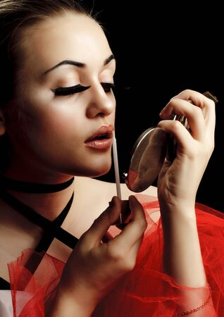 Fashion Model with Lip Gloss and Hand Mirror photo