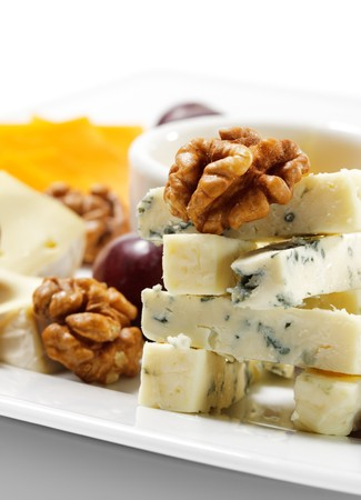 Various Types of Cheese with Honey Sauce and Grapes photo