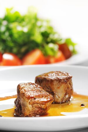 Hot Meat Dishes - Veal Medallions with Vegetable Plate on a Background Stock Photo