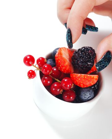 Fresh Berries Bowl and Beauty Woman Hand. Isolated on White Background photo