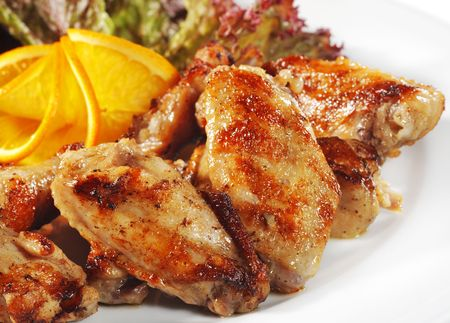 grill chicken: Fried Chicken Wings with Orange Slice and Vegetable Leaf