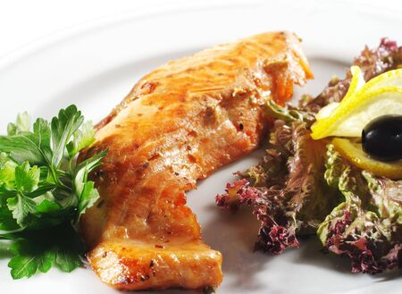 Hot Fish Dishes - Salmon Fillet with Fresh Salad Leaf and Parsley photo