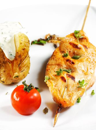 Chicken s Shish Kebab Served with Roast Potatoes and Cherry Tomato. Isolated on White Background photo