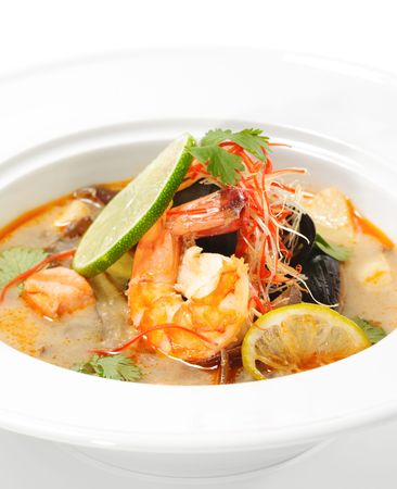 Thai Dishes - Tom Yam Kung. Spicy Shrimp Soup with Coconut milk, Lime and Seafood photo