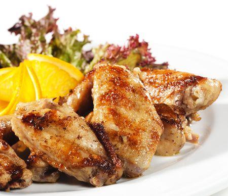 � chaud des plats de viande - Fried des ailes de poulet avec une tranche orange et l�gumes feuilles  Banque d'images