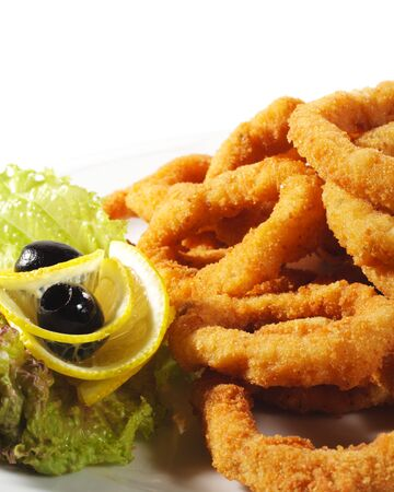 Seafood - Fried Calamari. Deep-fried Squid Dressed with Salad Leaves, Parsley, Olives and Lemon photo