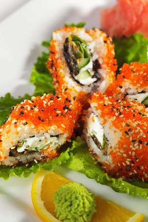 Sushi Roll with Eel, Fresh Cucumber, Salad Leaf and Cream Cheese inside. Tobiko (flying fish roe) and Sesame outside Stock Photo - 5925261