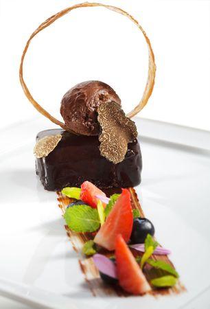 Ganache Dessert - Sweet mixture of Chocolate and Heavy Cream. Garnished with Tartufo Bianco (white truffle mushroom), Fresh Mint Leaf and Berries photo