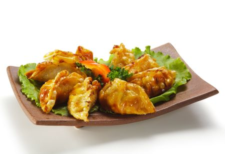 gyoza: Japanese Cuisine - Pork (or Seafood) Dumplings (gyoza). Garnished on Salad Leaf with Pepper and Fresh Parsley