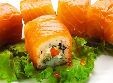 Roll with Cream Cheese, Salmon roe (ikura) and Cucumber inside. Salmon and outside. Served on Salad Leaf photo