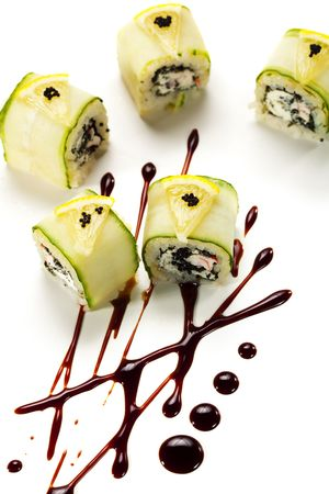 Cucumber Maki Sushi  - Roll made of Imitation Crab, Cream Cheese and Black Tobiko (flying fish roe) inside. Cucumber outside. Topped with Lemon Slice and Tobiko. Served on Sauce Pattern photo